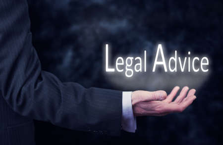 A businessmans hand holding the words, Legal Advice.