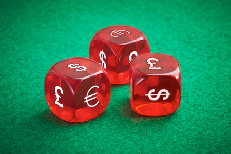Currency exchange rate concept, three red dice on a green felt background. photo