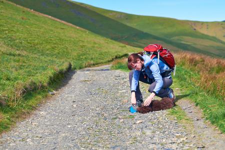 injure: A female hiker checkingan injured dog that is lying down.