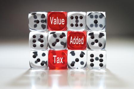 BTW-concept, drie rode dobbelstenen met Value, Added Tax en in een muur van duidelijke dobbelstenen.