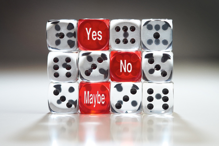 Chance concept, three red dice with Yes, No and Maybe in a wall of clear dice. photo