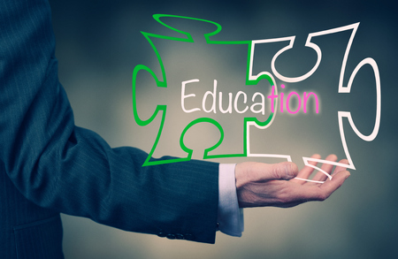 A Businessmans hand holding the word Education. photo