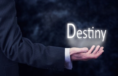A businessmans hand holding the word, Destiny.