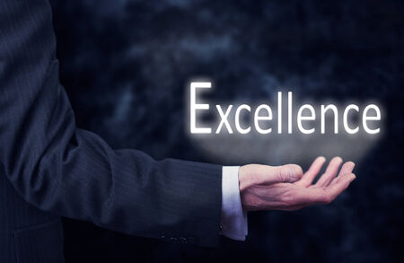A businessmans hand holding the word, Excellence.