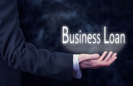 underwriter: A businessmans hand holding the words, Business Loan.
