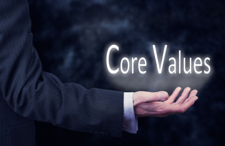 A businessmans hand holding the words, Core Values. Stock Photo