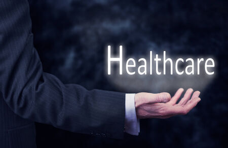 A businessmans hand holding the word, Healthcare. photo