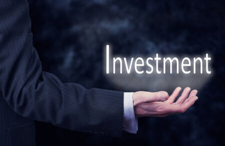 A businessmans hand holding the word, Investment.