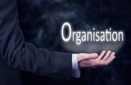 organisation: A businessmans hand holding the word, Organisation.