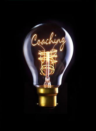 Coaching-Konzept in einem Filament Glühbirne. Lizenzfreie Bilder