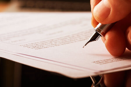 A hand holding a fountain pen and about to sign a letter. Styling and small amount of grain applied.