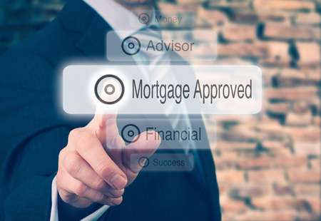 press agent: Businessman pressing a Mortgage Loan Approval concept button. Stock Photo