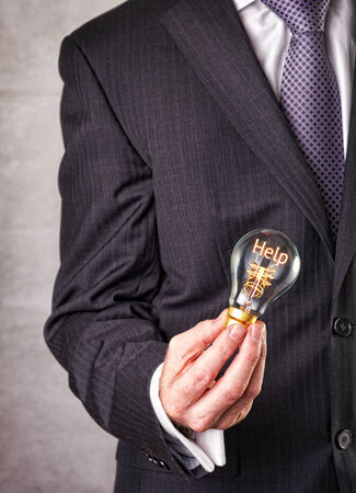Help concept in a filament lightbulb. Stock Photo
