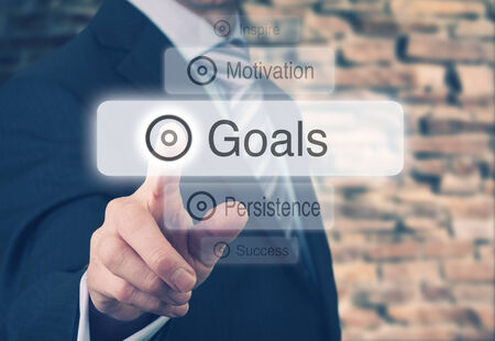Businessman pressing a Goals concept button.  photo