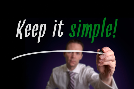 coherent: A businessman writing Keep It Simple on a screen. Business Concept. Stock Photo