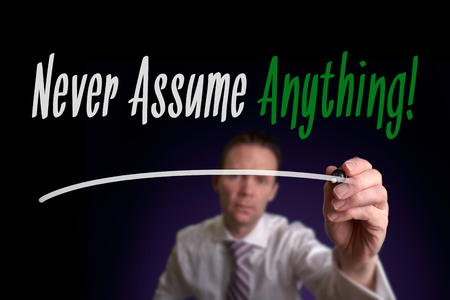 assume: A businessman writing Never Assume Anything on a screen. Life Concept