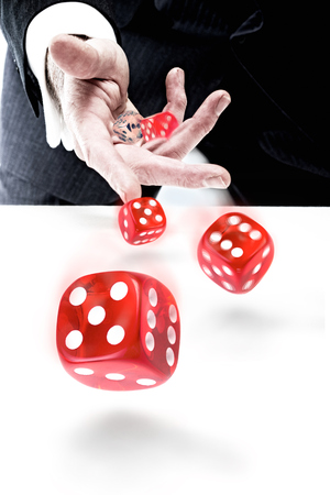 A closeup of a businessman throwing dice. Risk Concept. Standard-Bild