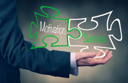 achieved: Businessman holding a Motivation concept puzzle. Stock Photo