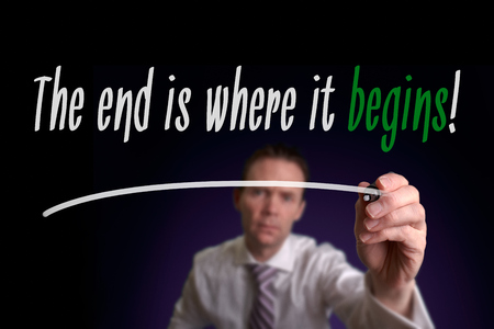 commencement: A businessman writing The End Is Where It Begins on a screen. Business Concept.