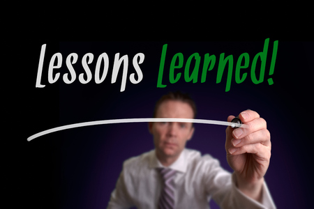 recap: A businessman writing Lessons Learned on a screen. Business Concept. Stock Photo
