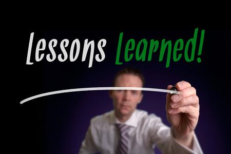 Un homme d'affaires écrit leçons apprises sur un écran. Concept.