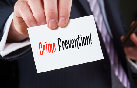 preventing: A businessman holding a business card with the words,  Crime Prevention, written on it.