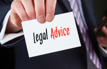 seeking assistance: A businessman holding a business card with the words, Legal Advice, written on it.