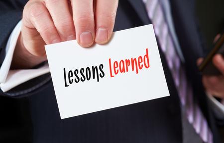 Een zakenman die een visitekaartje met de woorden, Lessons Learned, geschreven op het. Stockfoto