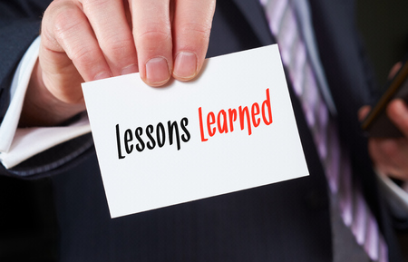 A businessman holding a business card with the words,  Lessons Learned, written on it.