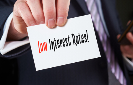 A businessman holding a business card with the words, Low Interest Rates, written on it.