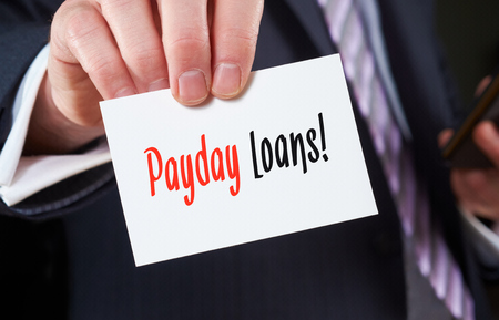 underwriter: A businessman holding a business card with the words, Payday Loans, written on it.