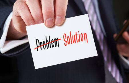 A businessman holding a business card with the words, Problem  Solution, written on it. photo