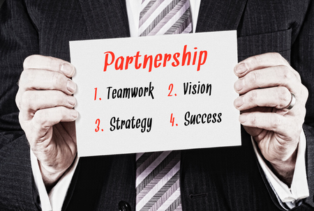 synergism: A businessman holding a business card with a Partnership Concept written on it.