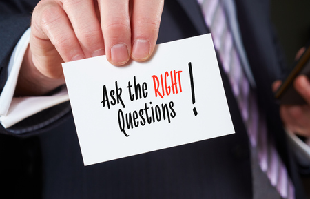 A businessman holding a business card with the words, Ask the Right Questions, written on it. Stockfoto