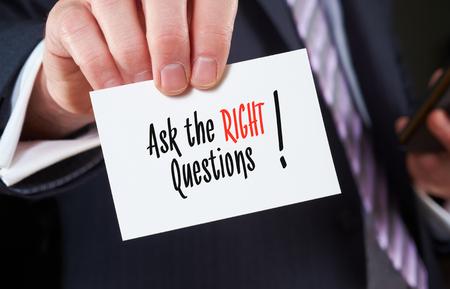 Ein Geschäftsmann hält eine Visitenkarte mit den Worten: Die richtigen Fragen stellen, auf der es geschrieben.