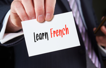 skillset: A businessman holding a business card with the words, Learn French, written on it. Stock Photo