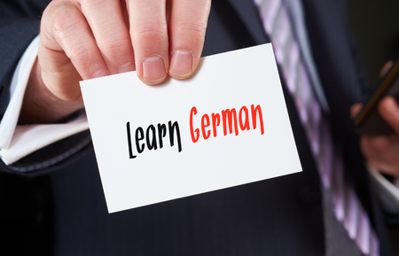 skillset: A businessman holding a business card with the words, Learn German, written on it.