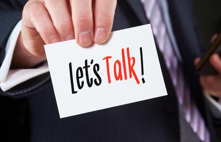 Een zakenman die een visitekaartje met de woorden, laten we praten, geschreven.