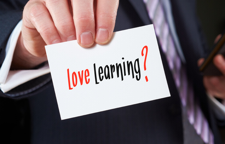 average guy: A businessman holding a business card with the words, Love Learning, written on it.