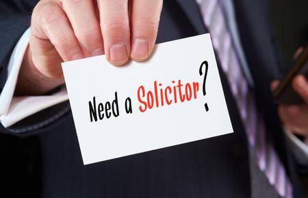 Een zakenman die een visitekaartje met de woorden, Noodzaak van een advocaat, op geschreven.
