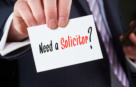 A businessman holding a business card with the words, Need a Solicitor, written on it.