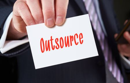 outsource: A businessman holding a business card with the words, Outsource, written on it. Stock Photo