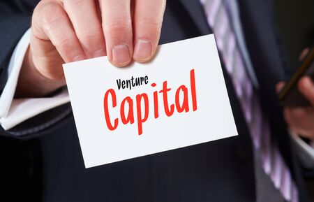 corporate greed: A businessman holding a business card with the words, Venture Capital, written on it. Stock Photo