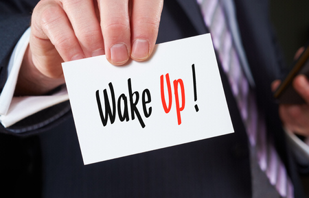 focalize: A businessman holding a business card with the words, Wake Up, written on it.