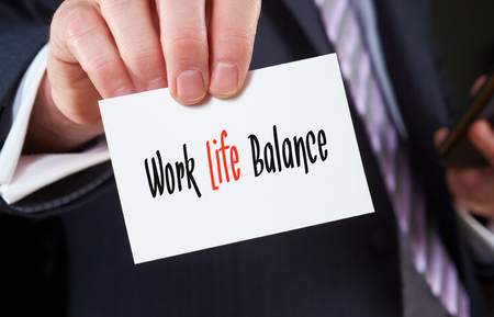 A businessman holding a business card with the words, Work Life Balance, written on it. photo