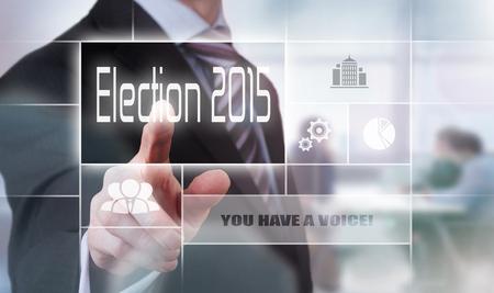 rhetorical: Businessman pressing an Election 2015 concept button.