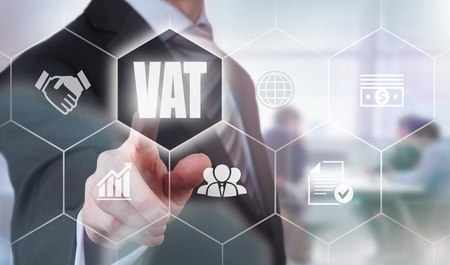 are added: Businessman pressing a VAT concept button. Stock Photo
