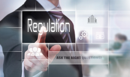 governing: Businessman pressing a Regulation concept button. Stock Photo