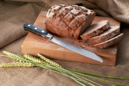Freshly baked traditional bread and knife on a wood board.