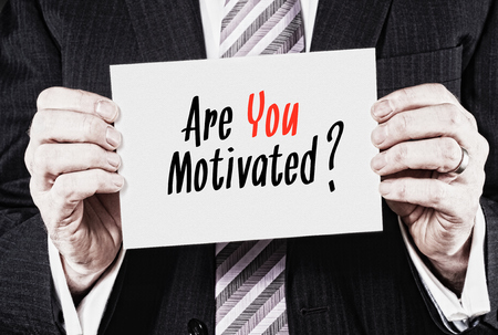 motivated: A businessman holding a card with the words,  Are You Motivated? Stock Photo